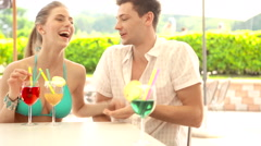 A young couple at water park in summer day is drinking cocktail at bar Arkistovideo