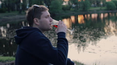 Man drinking wine sitting near the lake in the park Stock Footage