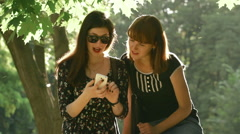 Cute girls talking in the park sitting on the parapet and surfing in social net Stock Footage