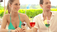 A young couple at water park in summer day is drinking cocktail at bar Stock Footage