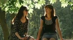 Cute girls talking in the park sitting on the parapet Stock Footage