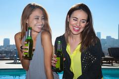 Two young adult female friends drinking beers at rooftop bar with Los Angeles - stock photo