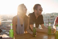 Two adult friends drinking beer at rooftop bar table with Los Angeles skyline, - stock photo