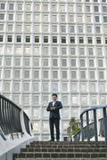 Low angle view of business man standing at top of stairway looking at watch Kuvituskuvat