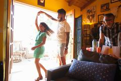 Girl dancing and twirling with father in living room - stock photo