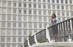 Business woman standing behind railings in front of built structure, using Stock Photos