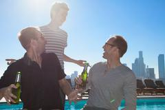 Three adult male friends drinking beers at rooftop bar with Los Angeles skyline, - stock photo
