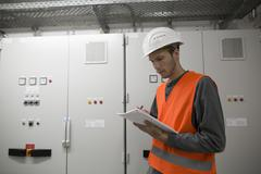 Young male engineer reading paperwork in technical room Kuvituskuvat