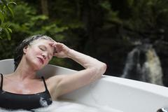 Mature woman with eyes closed in bubble bath in front of waterfall at eco - stock photo