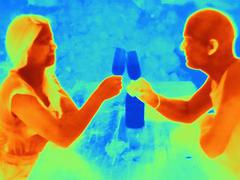 Thermal photograph of young couple raising a toast - stock photo