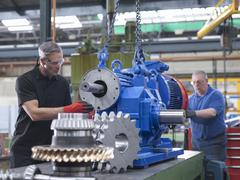Engineers assembling industrial gearbox in engineering factory Stock Photos