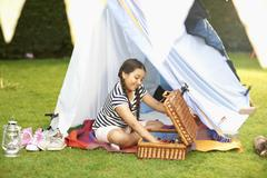 Girl emptying picnic basket in front of homemade tent in garden Stock Photos