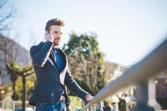 Young man talking on smartphone whilst holding railing Stock Photos