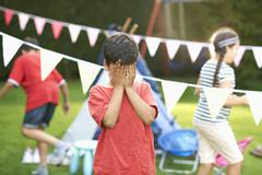 Boy covering his eyes for hide and seek with brother and sister in garden Stock Photos