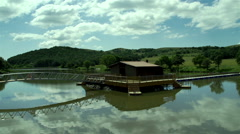 view of the natural landscape with wooden house in the middle of the lake - stock footage