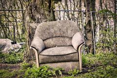 old dirty armchair in front of a tree - stock photo