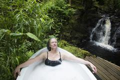 Mature woman relaxing in bubble bath in front of waterfall at eco retreat Stock Photos