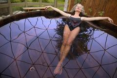 Mature woman lying back in hot tub at eco retreat Stock Photos