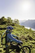 Young woman on mountain bike, looking at view, Lake Como, Italy Stock Photos