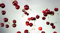 Juicy red cherry flies, rotates in the air and falls with slow motion over white Stock Footage