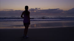 Ethnic American female doing a fitness workout running on the beach at sunrise Stock Footage
