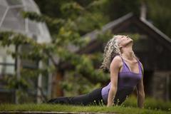 Mature woman practicing yoga upward dog in eco lodge garden - stock photo