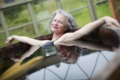 Portrait of mature woman relaxing in hot tub at eco retreat - stock photo