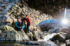 Young couple hiking, resting under bridge, Ashness Bridge, Keswick, Lake - stock photo