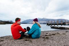 Young couple hiking, sitting by waters edge, Derwent Water, Keswick, Lake - stock photo