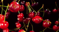 Close-up of cherry flies through the air and rotates a black background Stock Footage