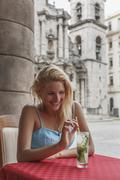Young woman with a Mojito cocktail in a restaurant on the Plaza de la Cathedral - stock photo