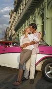 Young couple leaning against vintage convertible, Havana, Cuba - stock photo