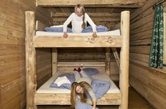 Two young women friends fooling around on bunk beds in log cabin Stock Photos