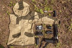 Overhead still life of camouflage anorak and photography equipment - stock photo