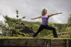 Mature woman practicing warrior pose in eco lodge garden - stock photo