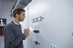 Young male technician making notes in technical room Kuvituskuvat