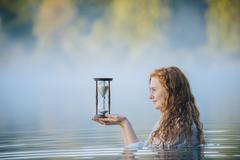 Young woman standing in misty lake gazing at hourglass - stock photo