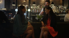 4K Female friends chatting & bartender serving drinks in trendy city bar Stock Footage