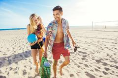 Young couple walking on beach, ready for picnic Stock Photos