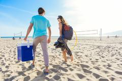 Young couple walking on beach, holding cool box, rear view Stock Photos