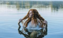 Head and shoulders of beautiful young woman with long red hair in lake - stock photo