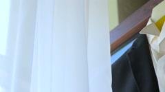 Groom's jacket on hanger on window near white tulle Stock Footage