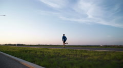 The guy's running at sunset on the sidewalk - stock footage