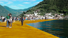 People walking along The Floating Piers work of art on Lake Iseo Stock Footage