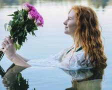 Head and shoulders of young woman with long red hair in lake gazing at bunch of - stock photo