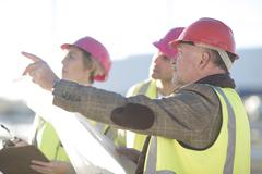 Architect and surveyors meeting on construction site Stock Photos
