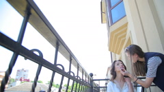Makeup artist paints lips for bride on the balcony - stock footage