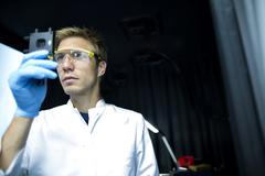 Male scientist holding up and scrutinizing specimen in lab cleanroom Stock Photos