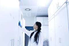 Female scientist opening sample cupboard in laboratory Stock Photos