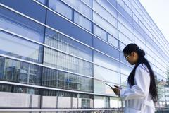 Young female scientist looking at digital tablet outside laboratory - stock photo